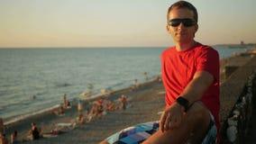 Jonge knappe mens die in zonnebril dichtbij het overzeese strand bij zonsondergang ontspannen Hij bewondert de zonsondergang en h stock videobeelden