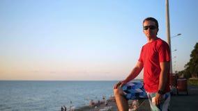 Jonge knappe mens die in zonnebril dichtbij het overzeese strand bij zonsondergang ontspannen Hij bewondert de zonsondergang en h stock video