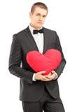 Jonge knappe mens die zwart kostuum dragen en een rood hart houden Stock Foto
