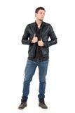 Jonge knappe mens in jeans die zwart leerjasje dragen die weg eruit zien stock fotografie