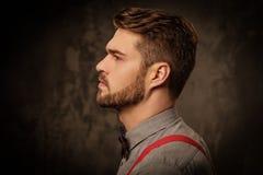 Jonge knappe mens met baard die bretels dragen en op donkere achtergrond stellen Stock Afbeelding