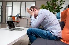 Jonge knappe mens met computer in het bureau Stock Afbeeldingen