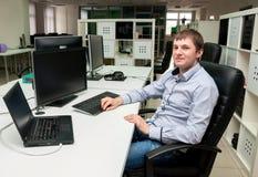 Jonge knappe mens met computer in het bureau Stock Foto's