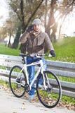 Jonge knappe mens met een fiets stock foto's