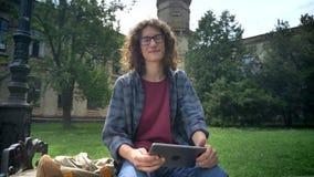 Jonge knappe mens met krullend lang haar in glazen die tablet houden en camera bekijken, die op bank in park dichtbij zitten stock videobeelden