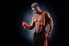 Jonge knappe mens met sterke spieren, eiwitdrank na trai Stock Foto's