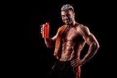 Jonge knappe mens met sterke spieren, eiwitdrank na trai Stock Fotografie