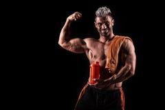 Jonge knappe mens met sterke spieren, eiwitdrank na trai Royalty-vrije Stock Afbeelding