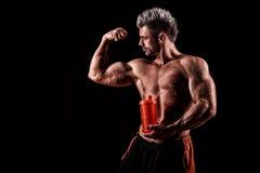 Jonge knappe mens met sterke spieren, eiwitdrank na trai Stock Afbeelding