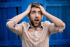 Jonge knappe mens in plaidoverhemd zenuwachtig over blauwe achtergrond royalty-vrije stock foto's