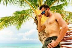 Jonge knappe mens in zonnebril bij het strand stock fotografie