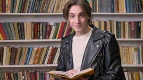 Jonge knappe mens in zwart de lezingsboek van het leerjasje in bibliotheek, het glimlachen, portret van het mannelijke student be stock video