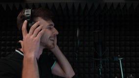 Jonge knappe pop zanger die aan camera glimlachen De aantrekkelijke jongen stijgt professionele hoofdtelefoons op stock videobeelden