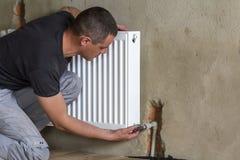 Jonge knappe professionele loodgieterarbeider die het verwarmen Ra installeren Stock Foto