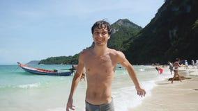 Jonge knappe speelse mensenlooppas op tropocal strand in langzame motie 1920x1080 stock footage