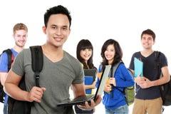 Jonge knappe student met laptop en vrienden bij de achtergrond royalty-vrije stock foto