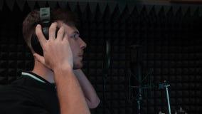 Jonge knappe vocale de muziekstudio van het kunstenaars zingende lied thuis met zwarte achtergrond Pop mannelijke stem van de zan stock footage