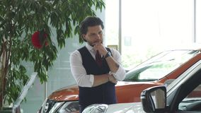 Jonge knappe zakenman die auto's voor verkoop onderzoeken bij het handel drijven stock video
