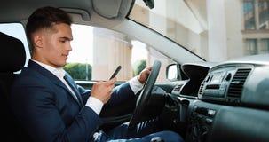 Jonge knappe zakenman die mobiele telefoon in de auto met behulp van De gelukkige jonge mens slaagt en schrijft een bericht Het c stock footage