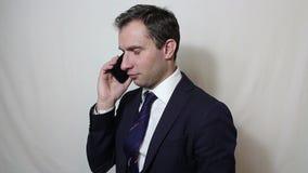 Jonge knappe zakenman die op zijn smartphone met een cli?nt spreken stock videobeelden