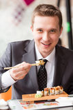 Jonge knappe zakenman die sushi met stokken eten Stock Foto's