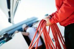 Jonge knappe zeeman die kabel op zeilboot trekken royalty-vrije stock foto's