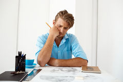 Jonge knappe zekere peinzende zakenmanzitting bij lijst die over het portret van de potloodtekening denken Wit modern bureau Stock Afbeelding