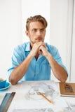 Jonge knappe zekere peinzende zakenmanzitting bij lijst die over het portret van de potloodtekening denken Wit modern bureau Royalty-vrije Stock Foto