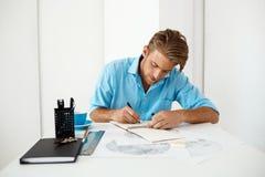 Jonge knappe zekere peinzende zakenmanzitting bij lijst met het portret van de potloodtekening Wit modern bureaubinnenland Royalty-vrije Stock Afbeelding