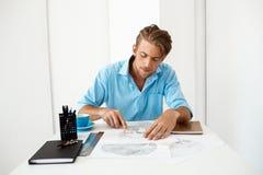 Jonge knappe zekere peinzende zakenmanzitting bij lijst met het portret van de potloodtekening Wit modern bureaubinnenland Stock Afbeelding