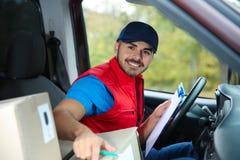 Jonge koerier die hoeveelheid pakketten controleren stock afbeeldingen