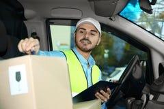 Jonge koerier die hoeveelheid pakketten controleren stock afbeelding