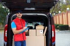 Jonge koerier die hoeveelheid pakketten in leveringsbestelwagen controleren stock afbeelding