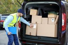 Jonge koerier die hoeveelheid pakketten in leveringsbestelwagen controleren stock foto