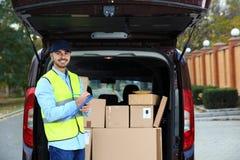 Jonge koerier die hoeveelheid pakketten in leveringsbestelwagen controleren stock fotografie