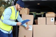 Jonge koerier die hoeveelheid pakketten in leveringsbestelwagen controleren royalty-vrije stock afbeeldingen