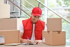 Jonge koerier die met documenten onder pakketten bij lijst werken stock afbeeldingen