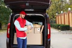 Jonge koerier met pakket en klembord dichtbij leveringsbestelwagen royalty-vrije stock foto's