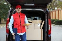 Jonge koerier met pakket en klembord dichtbij leveringsbestelwagen royalty-vrije stock foto