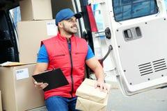 Jonge koerier met pakketten en klembord dichtbij leveringsbestelwagen royalty-vrije stock fotografie