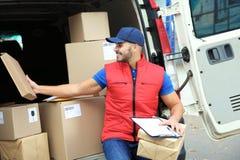 Jonge koerier met pakketten en klembord dichtbij leveringsbestelwagen stock afbeeldingen