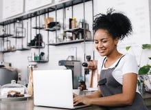 Jonge koffieeigenaar die aan haar laptop werken stock foto