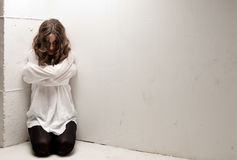 Jonge krankzinnige vrouw met dwangbuis op knieën Stock Afbeeldingen