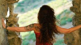 Jonge krullende vrouw die zich dichtbij het vestingsvenster bevinden stock footage