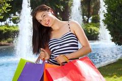 Jonge lachende vrouw die in de zomer winkelen. Stock Afbeelding