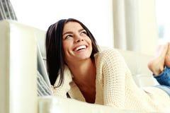 Jonge lachende vrouw die op de bank liggen Stock Foto's