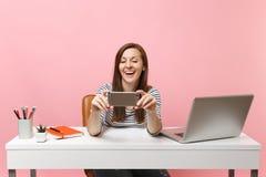 Jonge lachende vrouw die videogesprek maken die nemen doen selfie geschoten op mobiele telefoon terwijl het werk bij wit bureau m royalty-vrije stock afbeeldingen