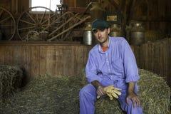 Jonge landbouwer die op horizontale hooiberg rusten, stock foto's