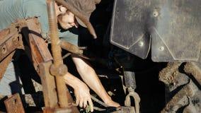 Jonge landbouwer die tractor voor het oogsten van aardappel bij gebied van organisch landbouwbedrijf voorbereiden Stock Foto