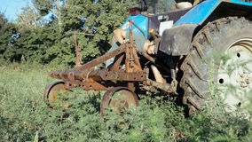 Jonge landbouwer die tractor voor het oogsten van aardappel bij gebied van organisch landbouwbedrijf voorbereiden Stock Fotografie